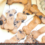A pin image of a pile of crunchy blueberry dog treats on a tile background.