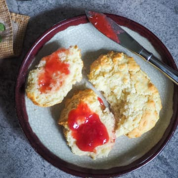 A drop biscuit cut in half with strawberry jam on top on a decorative plate.