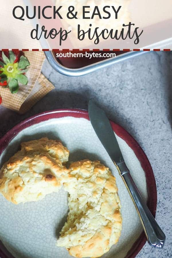 A pin image of a drop biscuit cut in half on a decorative plate with a jar of jam, extra biscuits, and three strawberries in the background.