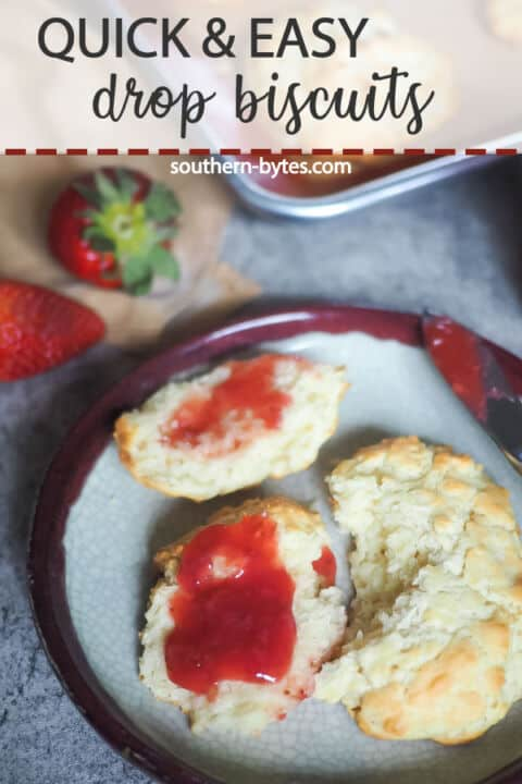 A pin image of a drop biscuit cut in half with strawberry jam on top on a decorative plate with a jar of jam and three strawberries in the background.