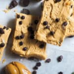 Peanut butter and chocolate chip perfect bars on a piece of parchment paper with a knife and a glob of peanut butter.