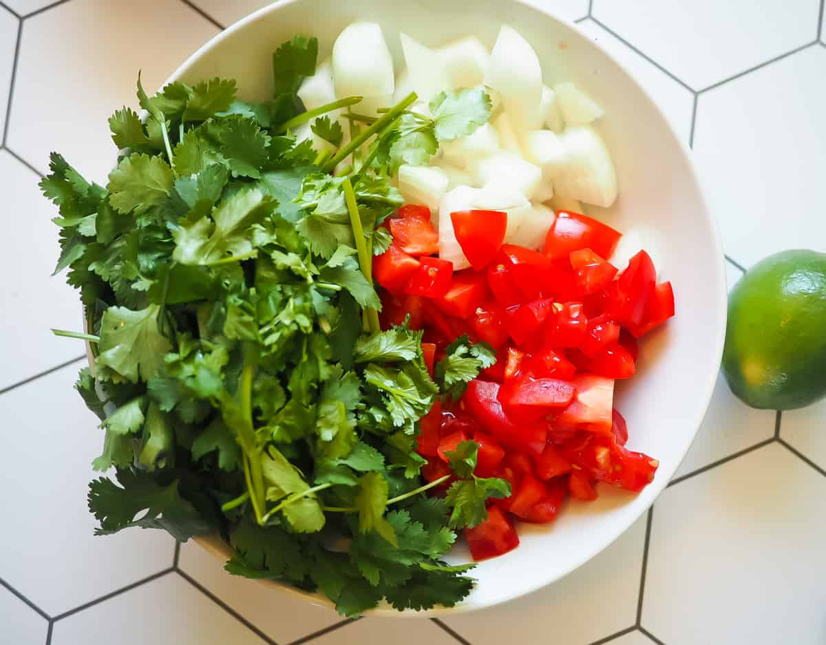 A white bowl with onion, tomato, and cilantro in it with a lime.