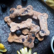 A pile of blueberry dog biscuits and blueberries on a gray background with a yellow flower and a yellow napkin.