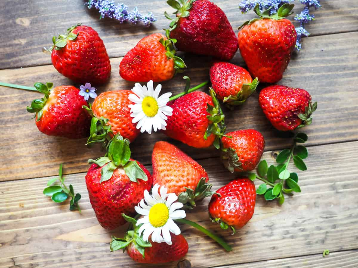 A bunch of overripe strawberries laid out on a wooden surface with daisies and purple flowers scattered around.