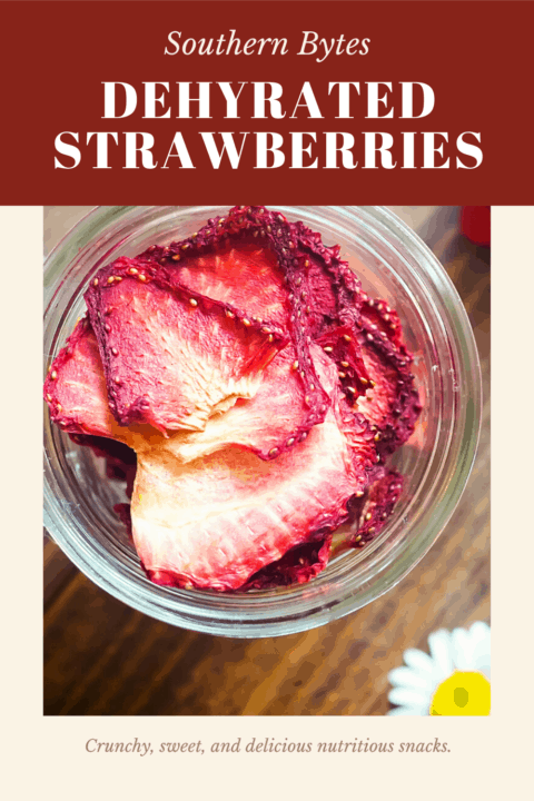 A pin image of a jar of dehydrated strawberries on a wood background with some daisies scattered around.