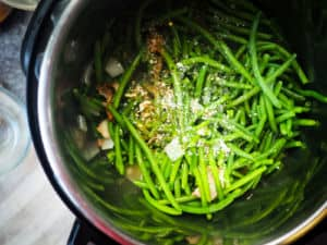 Green beans in an Instant Pot with seasoning on top.