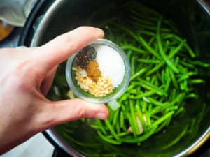 Green beans in an Instant Pot with a hand holding a small bowl of seasoning above it