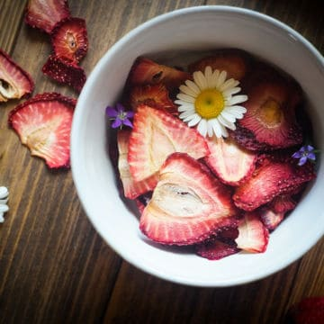 A bowl of dehydrated strawberries on a wood background with some daisies and small purple flowers scattered around.