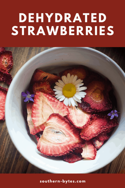 A pin image of a bowl of dehydrated strawberries on a wood background with some daisies and small purple flowers scattered around.