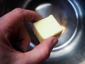 A hand holding a cube of butter over an Instant Pot.
