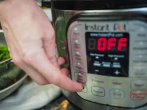 Someone pushing the saute button on an Instant Pot.