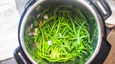 An Instant Pot with uncooked green beans in it.