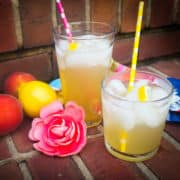 Two glasses of peach lemonade on brick steps with colored straws, peaches, a lemon, a pink flower, and lemon slices.