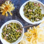 Two white bowls filled with southern green beans and bacon on a gray background with two yellow flowers and a yellow napkin.