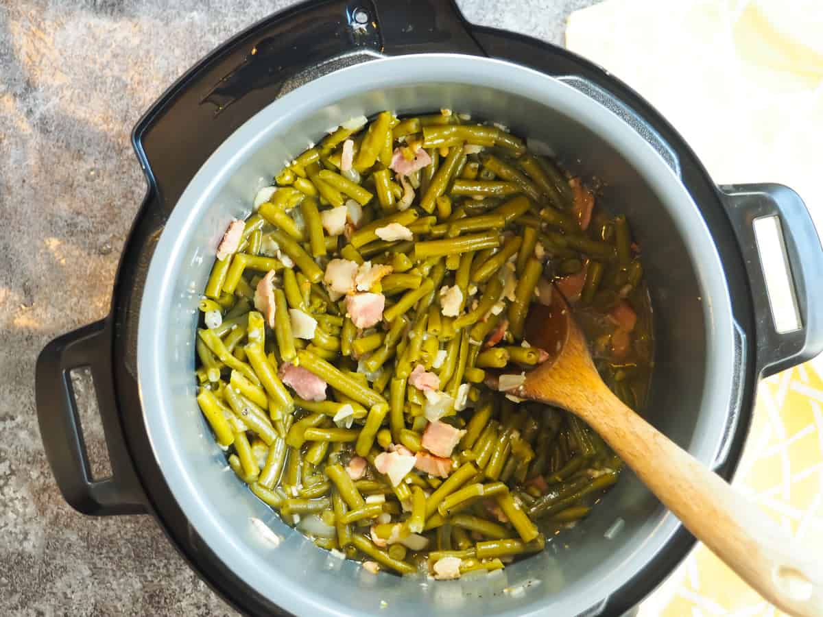 An instant pot with cooked southern green beans in it and a wooden spoon.
