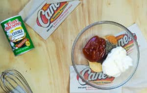 An unmixed bowl of Raising Cane's dipping sauce on a wood background with a whisk and container of Tony's Creole Seasoning next to it.