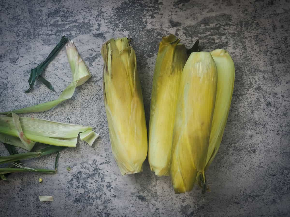four ears of cooked corn in their husks