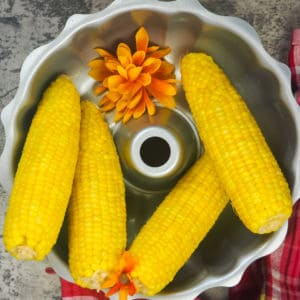 four cooked ears of corn in a silver bowl with orange flowers