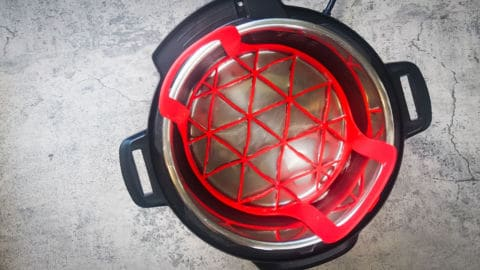 an instant pot with a red sling in it