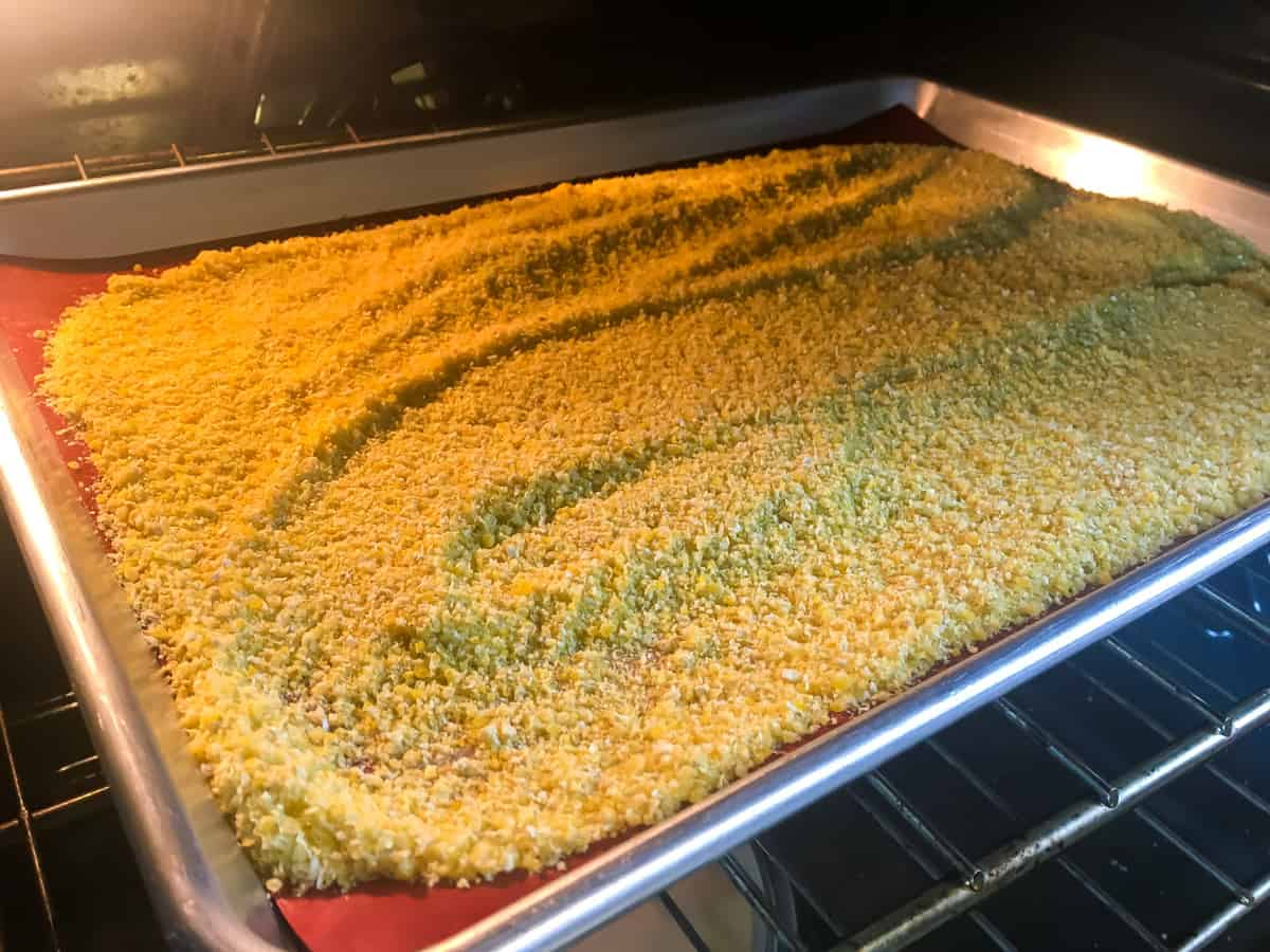 a baking sheet with homemade cornmeal spread on it in the oven