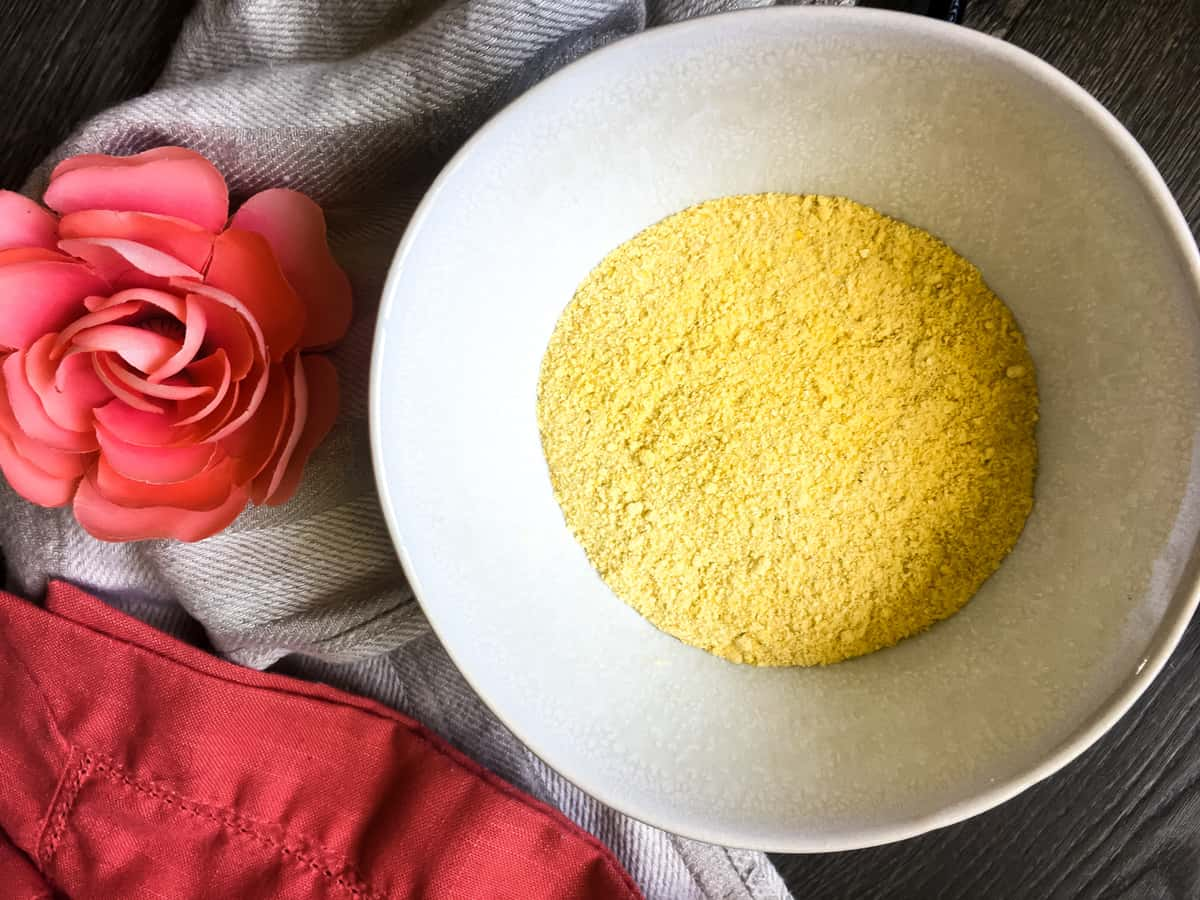 a white bowl of homemade cornmeal with a pink flower