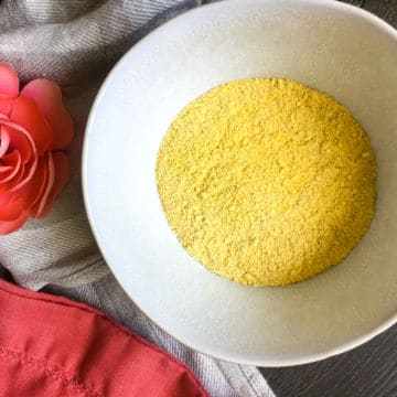 a white bowl of homemade cornmeal with a pink flower and a linen towel