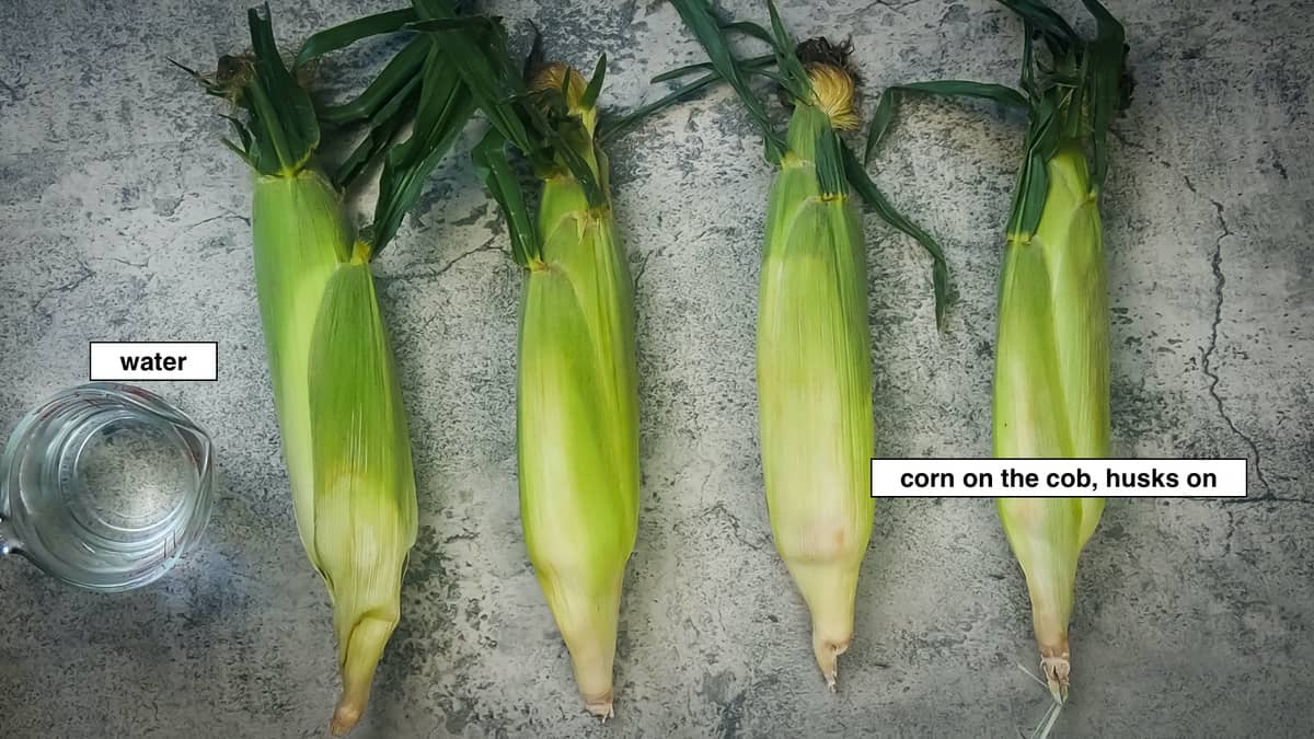 four ears of corn and a measuring cup of water, labeled
