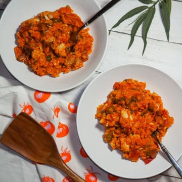 two white bowls of creole jambalaya with a wooden spoon