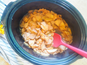 a crockpot with cooked apples coated in cinnamon in it.