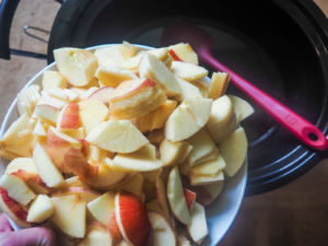 a bowl of sliced apples being dumped in a crock pot.