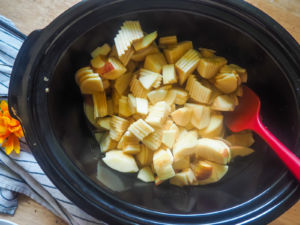 a crockpot with sliced apples in it.