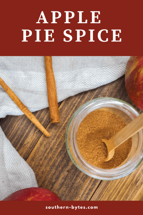 A pin image of a jar of apple pie spice with a small wooden spoon on top of the jar, two cinnamon sticks, and text overlay.