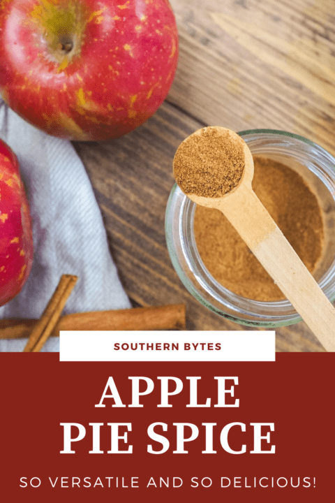 A pin image of a jar of apple pie spice with a small wooden spoon on top of the jar and some apples in the background.
