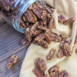 a spilled jar of candied pecans on a white and yellow napkin.