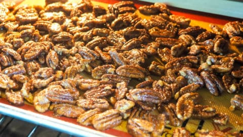 a tray of candied pecans baking in the oven.