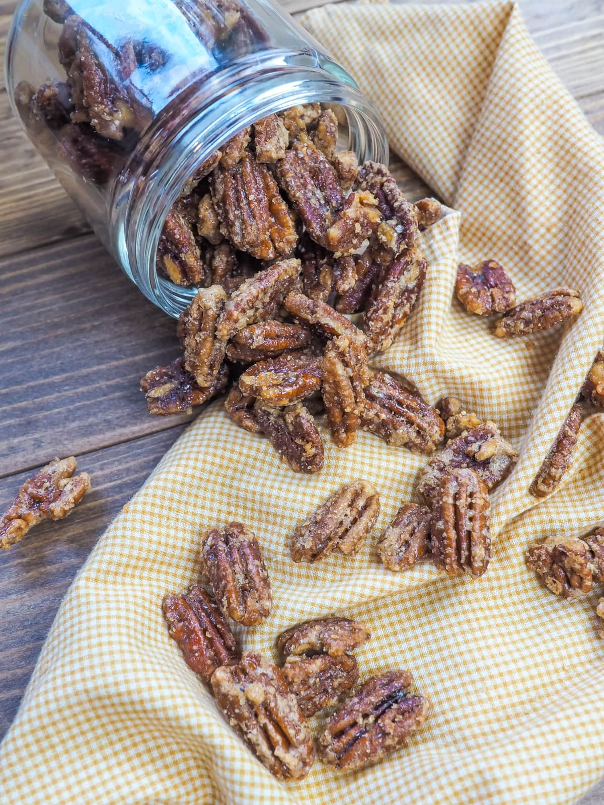a jar of spilled candied pecans and a yellow and white plaid napkin.