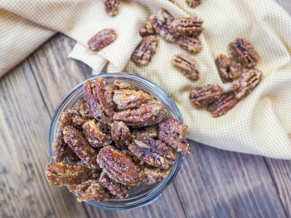 a jar of candied pecans and a yellow and white plaid napkin.