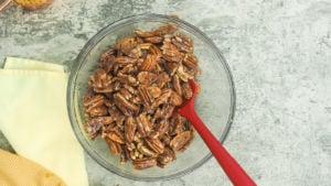 a clear bowl with egg white coated pecans in it.