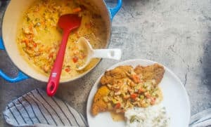 a white plate with fried catfish, crawfish etouffee, and green onion rice on it with a pot of crawfish etouffee