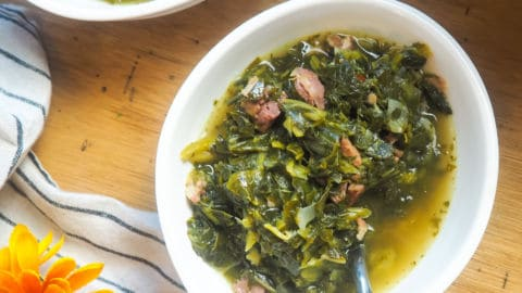 a white bowl of collard greens with bits of ham and bacon.