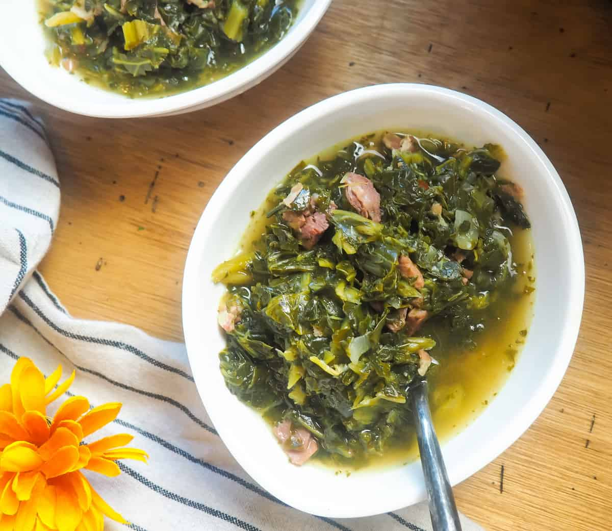 a white bowl of collard greens with bits of ham and bacon