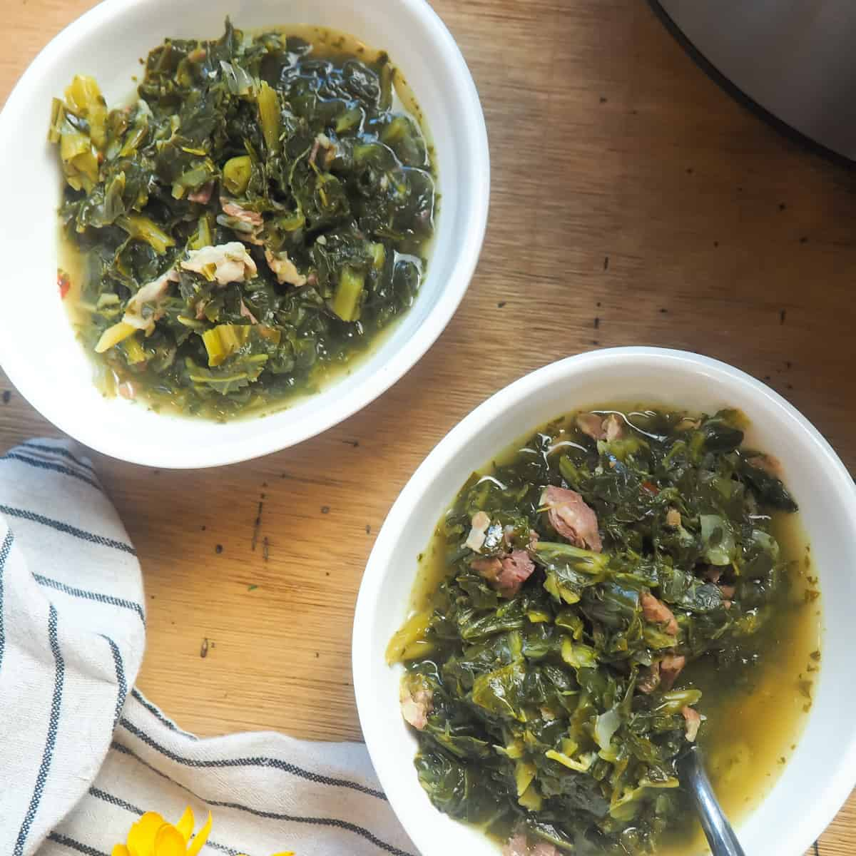 two bowls of collard greens with bits of ham and bacon.