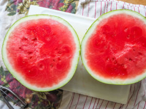 A watermelon cut in half on a white cutting board.