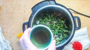 apple cider vinegar being poured into an instant pot of collard greens.