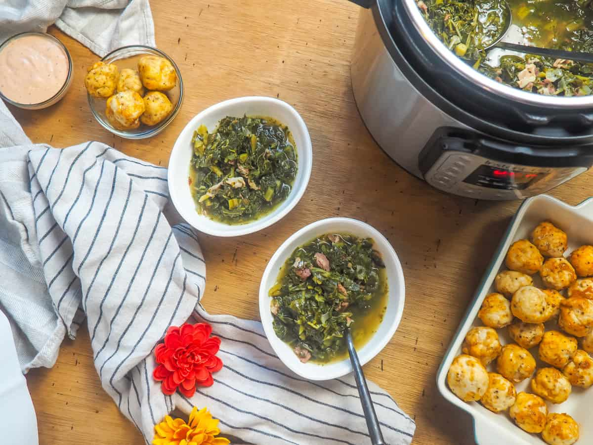 two bowls of collard greens next to an instant pot of collard greens and a pan of fried chicken balls.