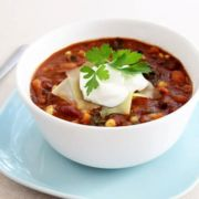 A bowl of three bean and sweet potato chili with a dollop of sour cream on top.