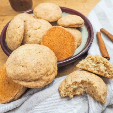 A pile of snickerdoodles on a plate with one broken in half in front of it.