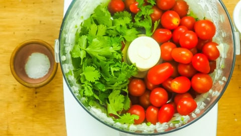 A food processor bowl with cherry tomatoes and cilantro in it.