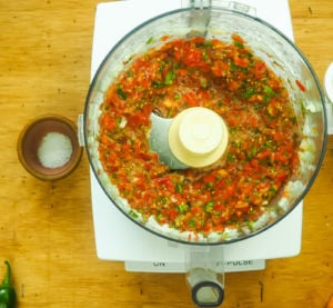 A food processor bowl with cherry tomato salsa in it.