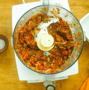 A food processor bowl with strained cherry tomato salsa in it.